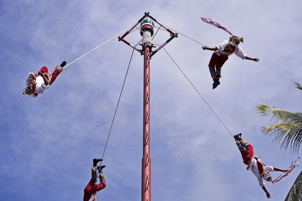 Four men seeming to dance in the air, attached by ropes to a very tall pole