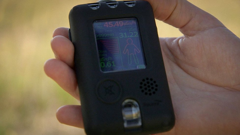 A researcher holds a radiation dosimeter