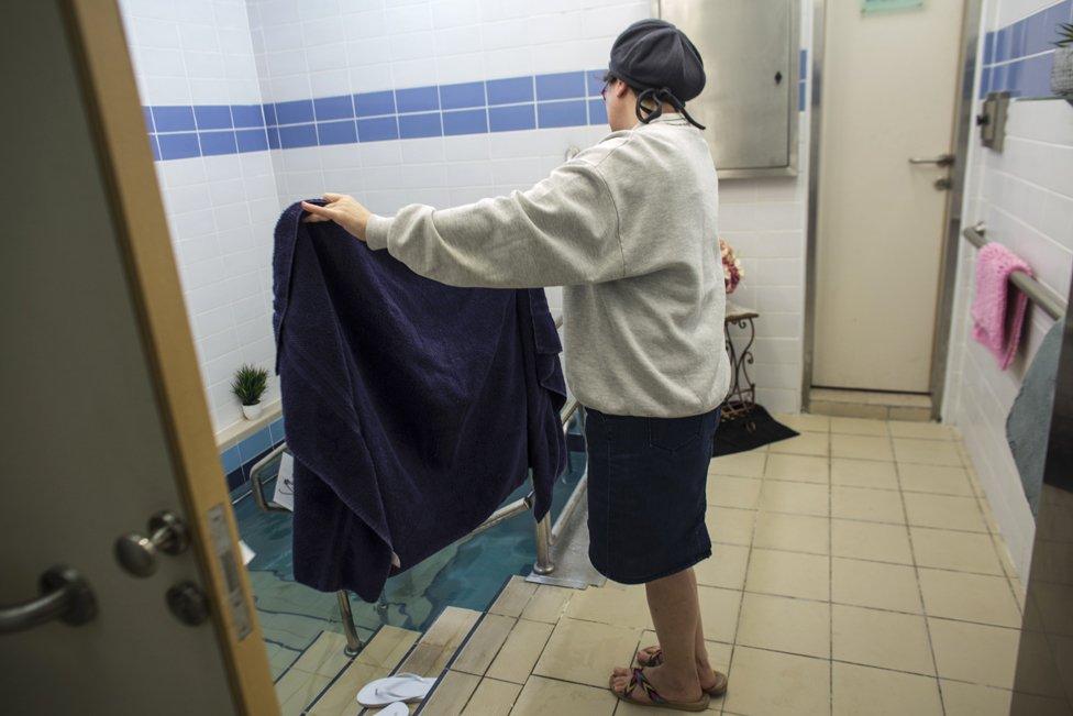 Balanit, poslužiteljka iz mikve, drži peškir za Jevrejku koja je ušla u vodu u mikve u Jerusalimu