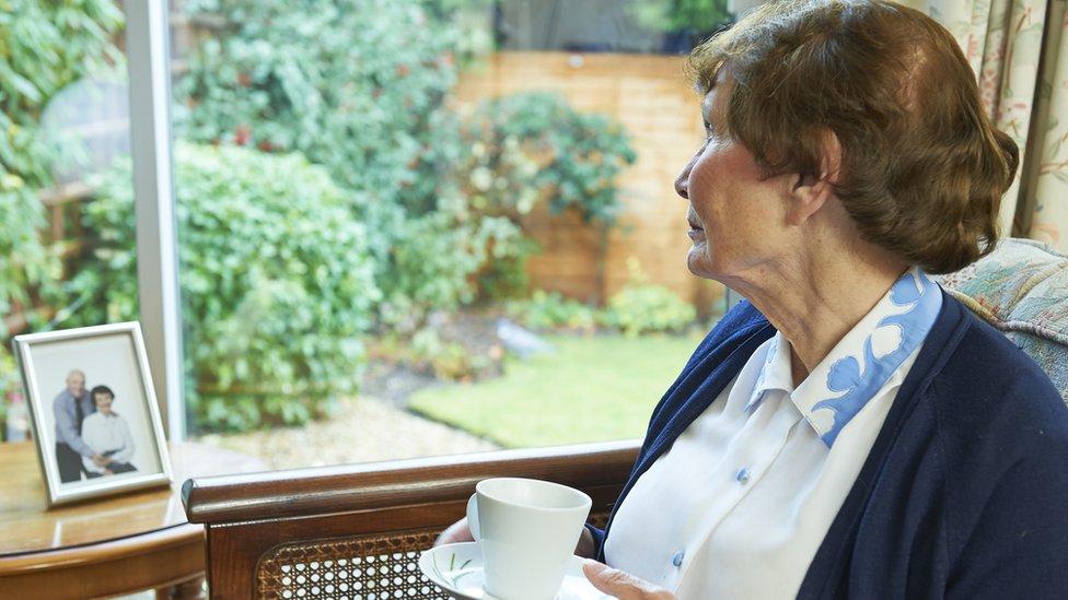 Žena gleda kroz prozor držeći šolju čaja