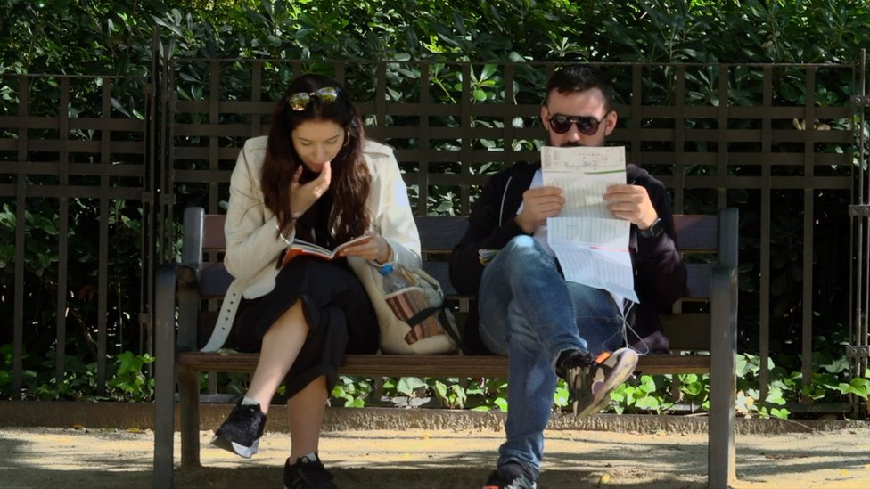 A man and a woman sit on a bench reading