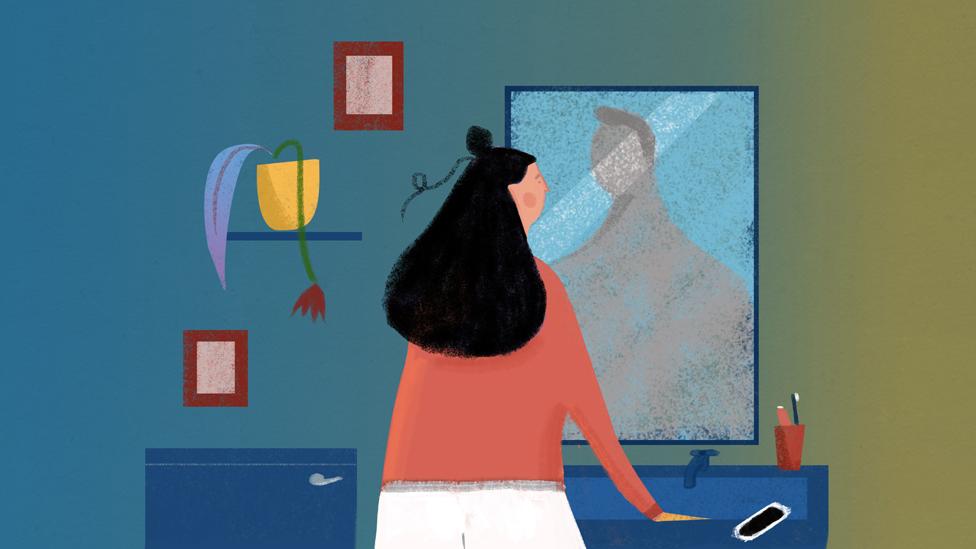 Woman looking in mirror in bathroom
