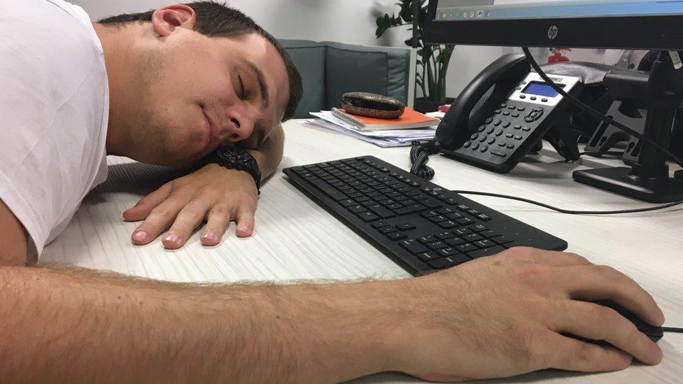 čovek spava za stolom