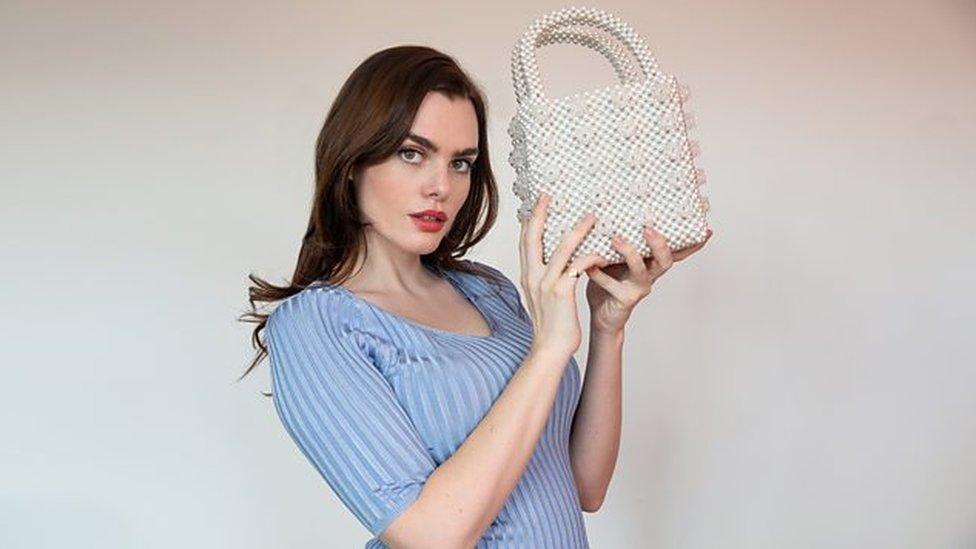 Charli holding a white beaded handbag - light grey background