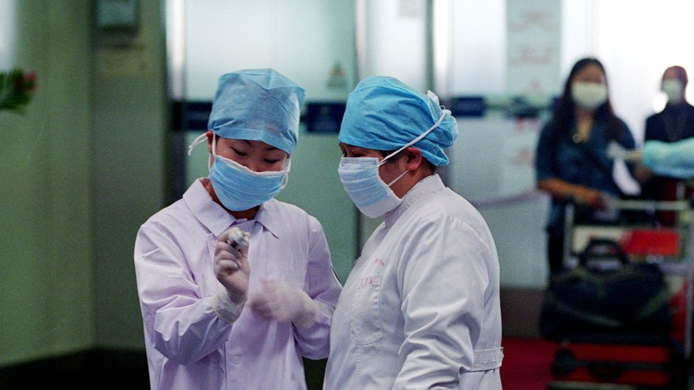 Nurses check a thermometer reading in the departure hall of the Beijing's Capital Airport April 28, 2003