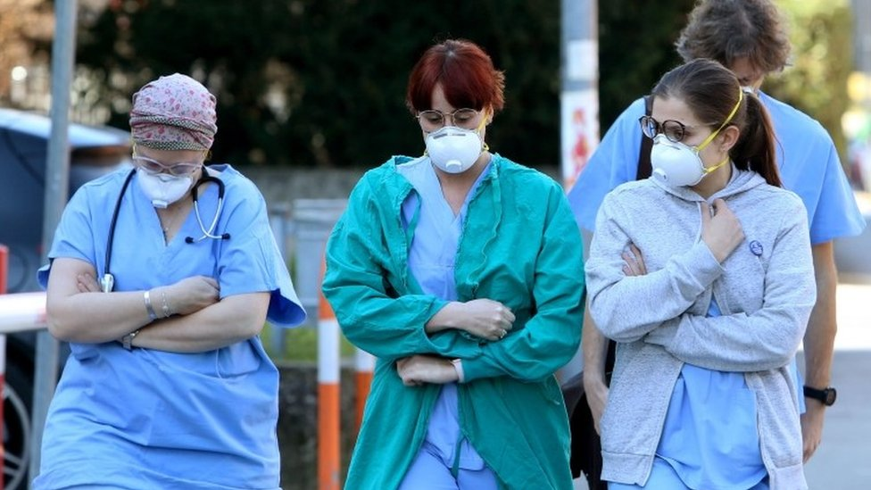 People and health workers wear protective face masks outside the hospital in Padua, Veneto region