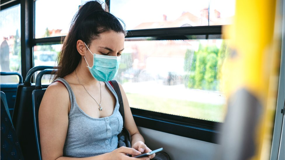 Woman wearing face mask on a bus