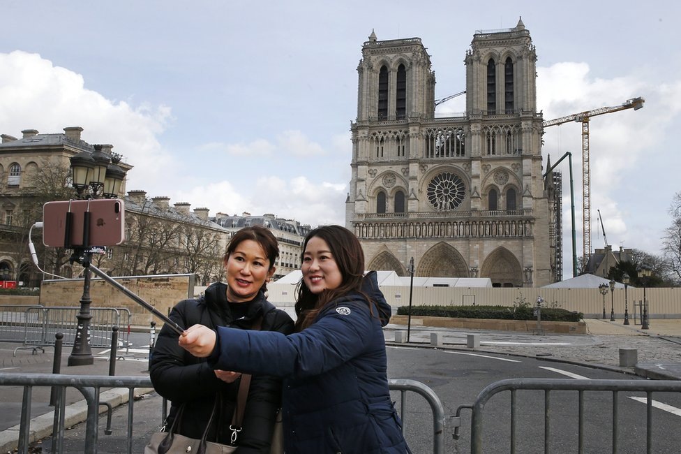Tourists take a photo with the Notre-Dame cathedral in the background