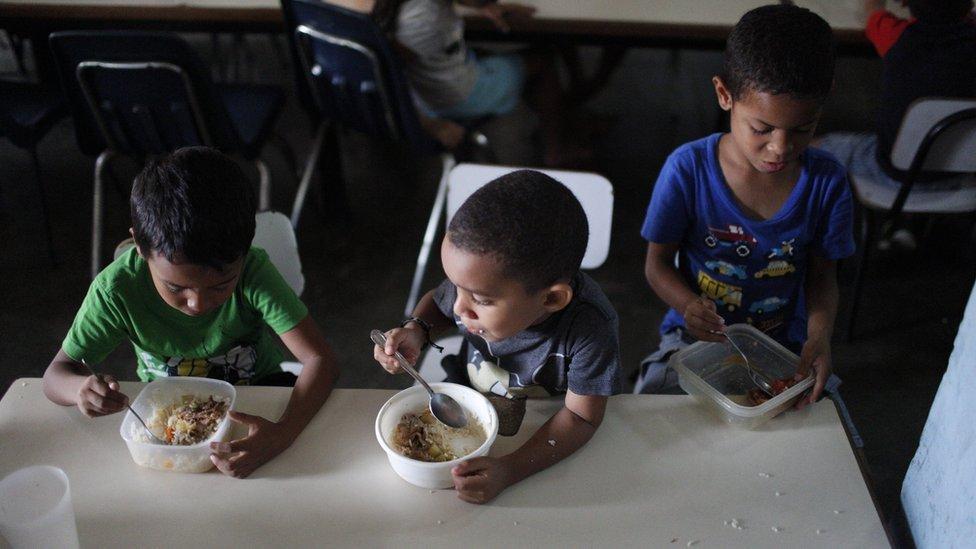 Children eat lunch at Madre Asuncion's community kitchen on October 9, 2019 in Petare, Caracas, Venezuela.