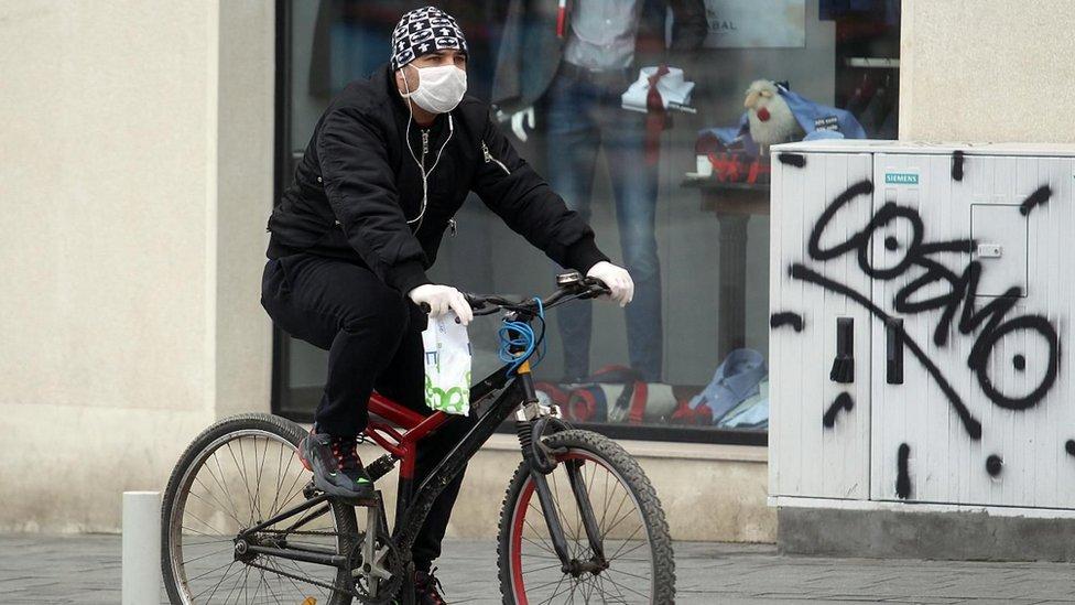 muškarac na biciklu sa maskom