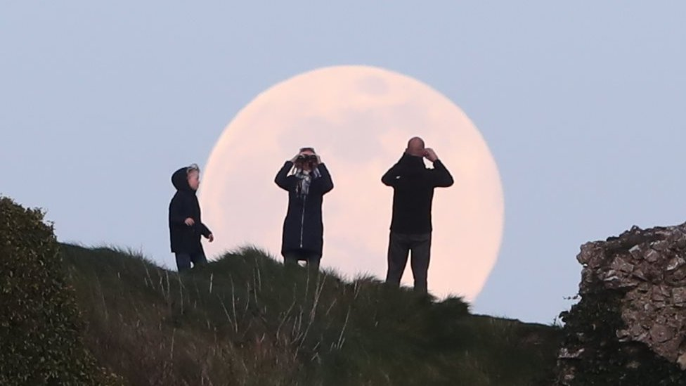 A pink supermoon rises over the Rock of Dunamase in County Laois in the Republic of Ireland