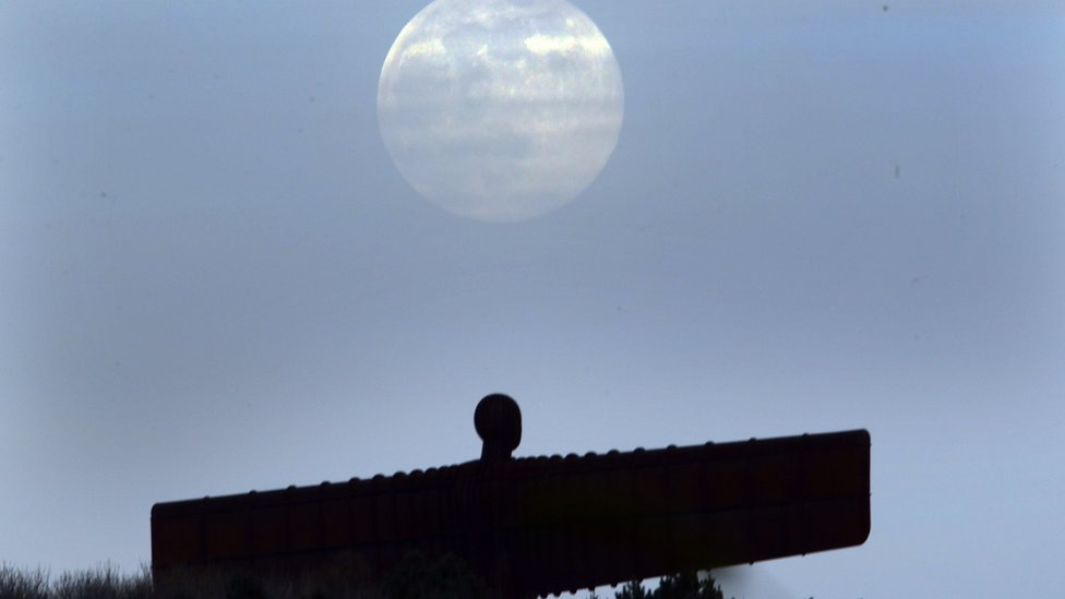 A pink supermoon is seen over the Angel of the North in Gateshead