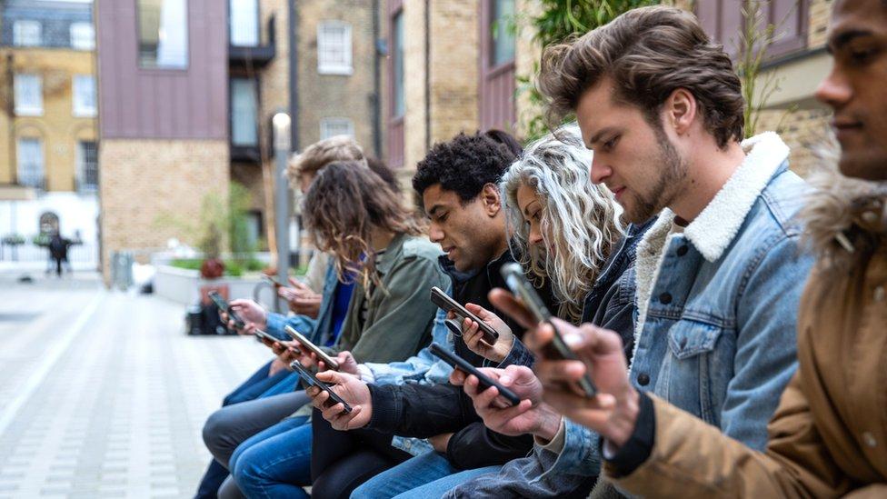 Mladi ljudi gledaju u telefon