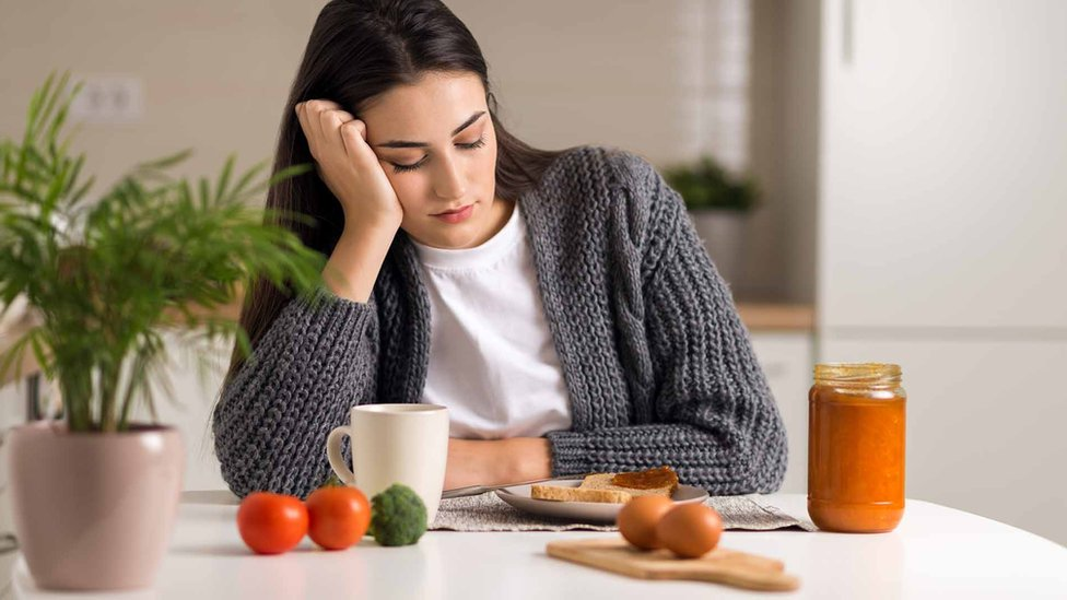 Young woman looks unhappily at food on her plate