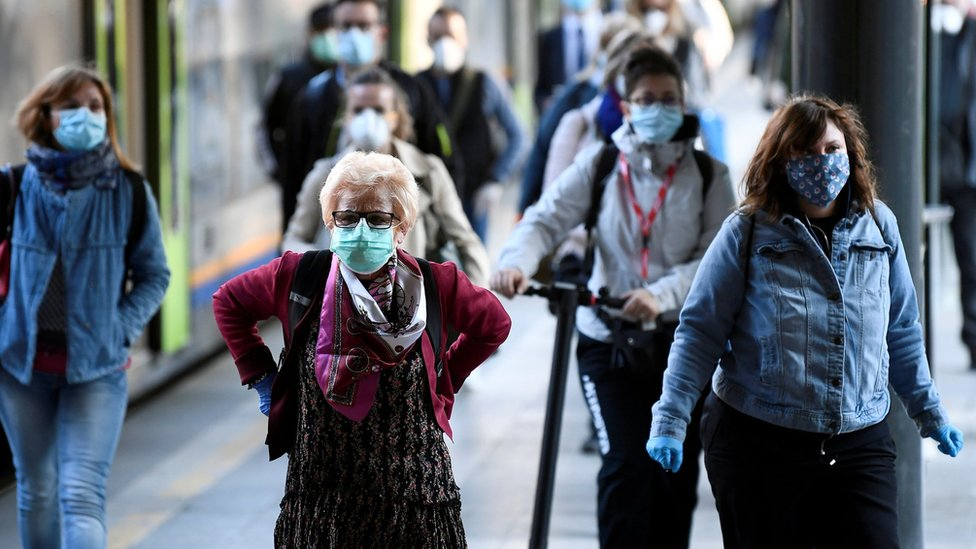 Passengers in masks arrive at a railway station in Milan (3 May)