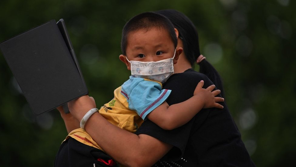 A mother holds his son next to Yangtze River in Wuhan, in Chinas central Hubei province on May 12, 2020. -