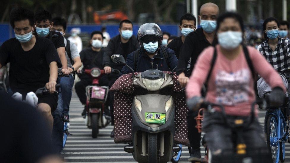 Residents wears face masks while riding their bicycles on May 11, 2020 in Wuhan, China.
