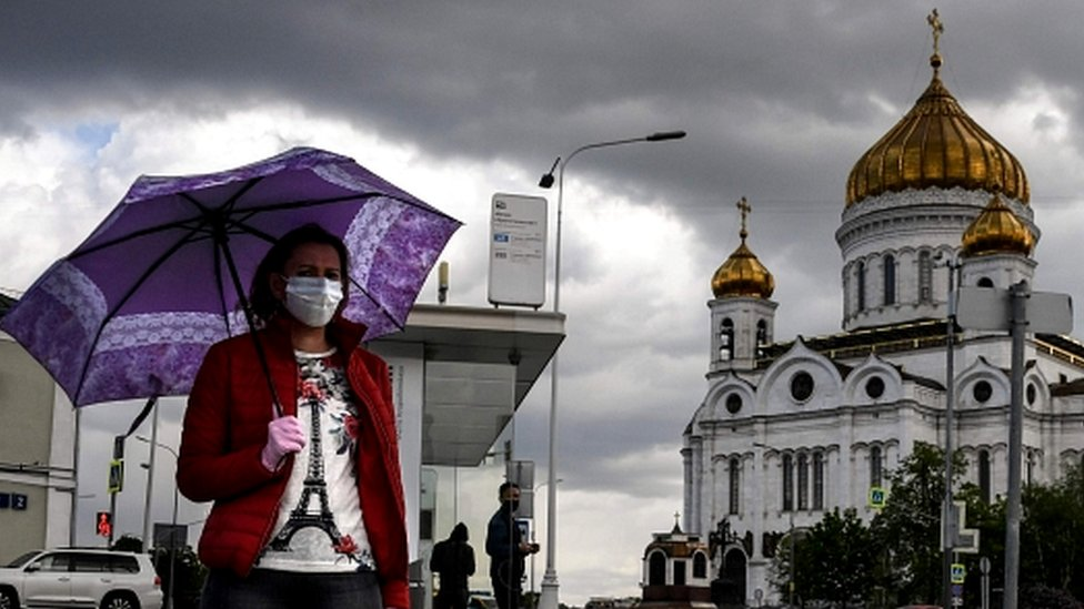 A woman walks past Christ the Savior cathedral in central Moscow on May 14, 2020