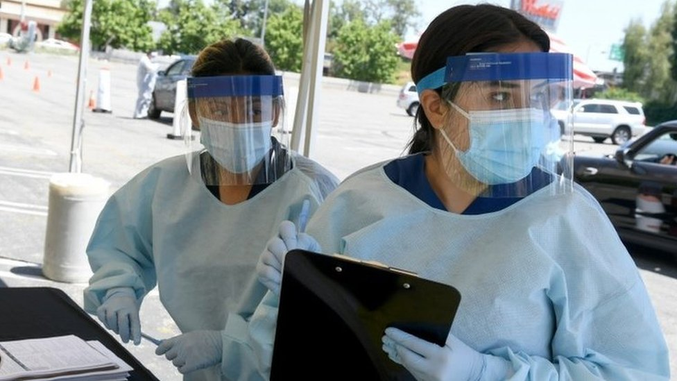 Health workers in PPE carry out coronavirus tests