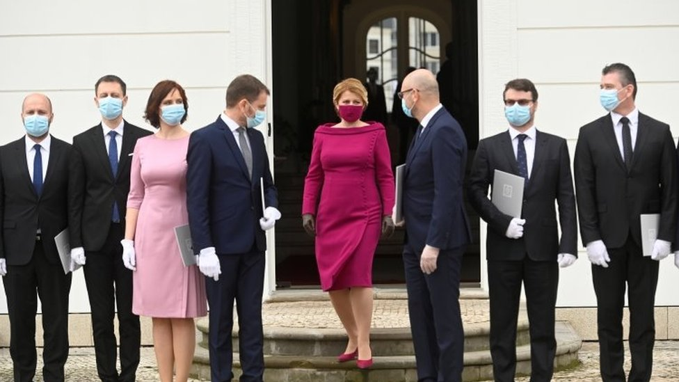 Slovakia's President Zuzana Caputova wears a protective face mask and poses for a photo with new members of the Slovak government
