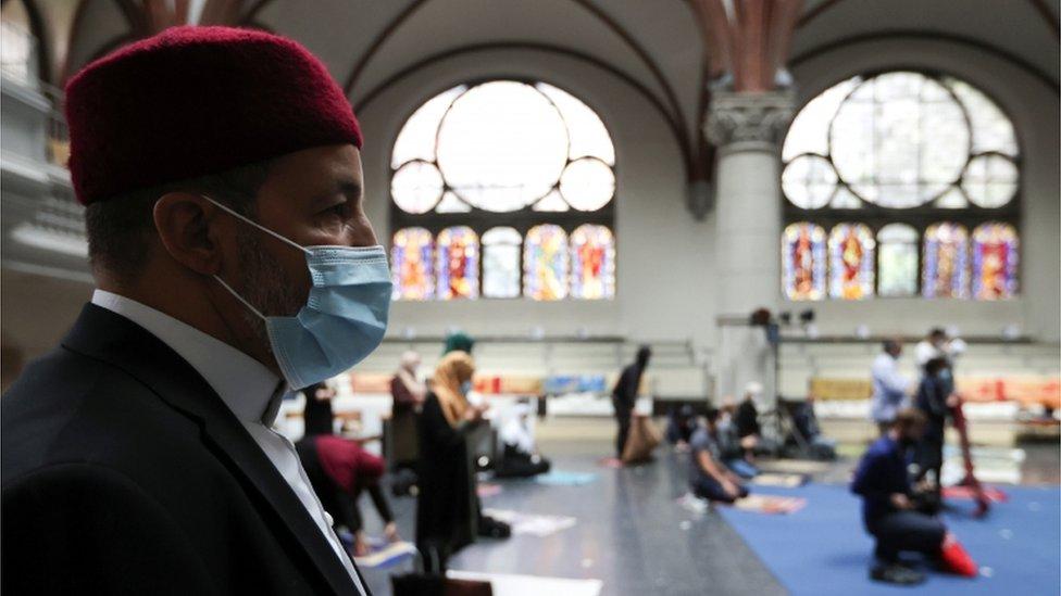 A Muslim man wearing a face masks prays at a church in Berlin