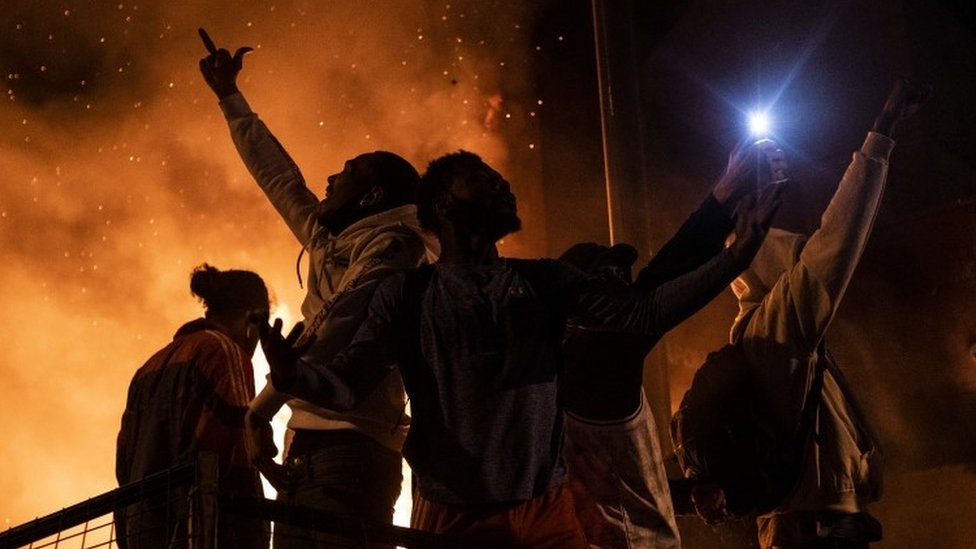 Protesters cheer as the Third Police Precinct burns behind them on 28 May 2020 in Minneapolis, Minnesota.