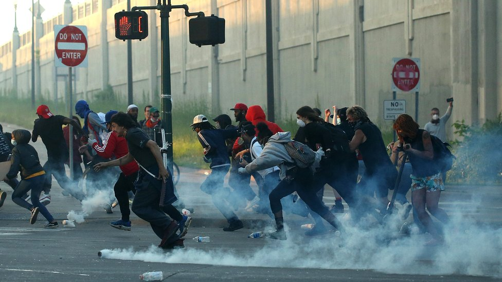 People run as tear gas canisters land near them during a protest sparked by the death of George Floyd while he was in police custody, in Minneapolis, Minnesota, 29 May 2020