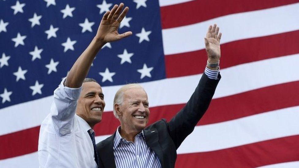 Barak Obama i Džo Bajden mašu, stojeći ispred američke zastave