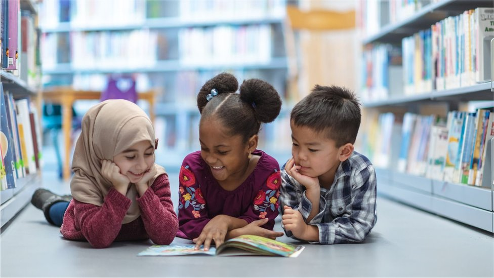Children read a book together in a library
