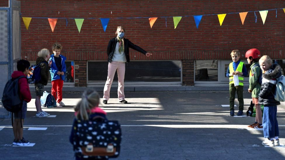 Pupils observe social distancing rules in a school playground in the Netherlands, 15 May 2020