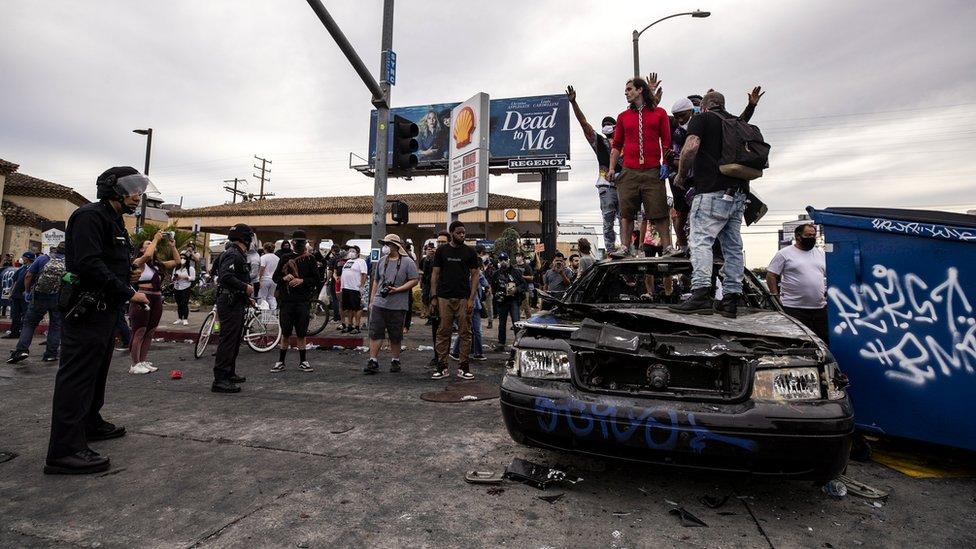 Demonstranti stoje na zapaljenom policijskom vozilu