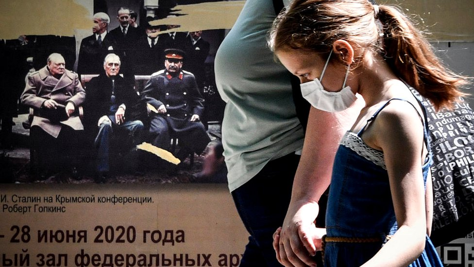 Girl walking past a poster showing World War Two leaders