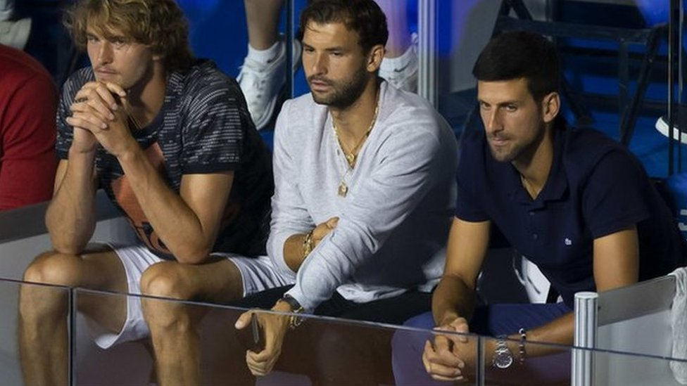 Grigor Dmitrov seated next to Novak Djokovic