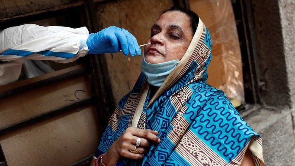 A woman wearing a headscarf undergoes a nose swab to detect Covid-19