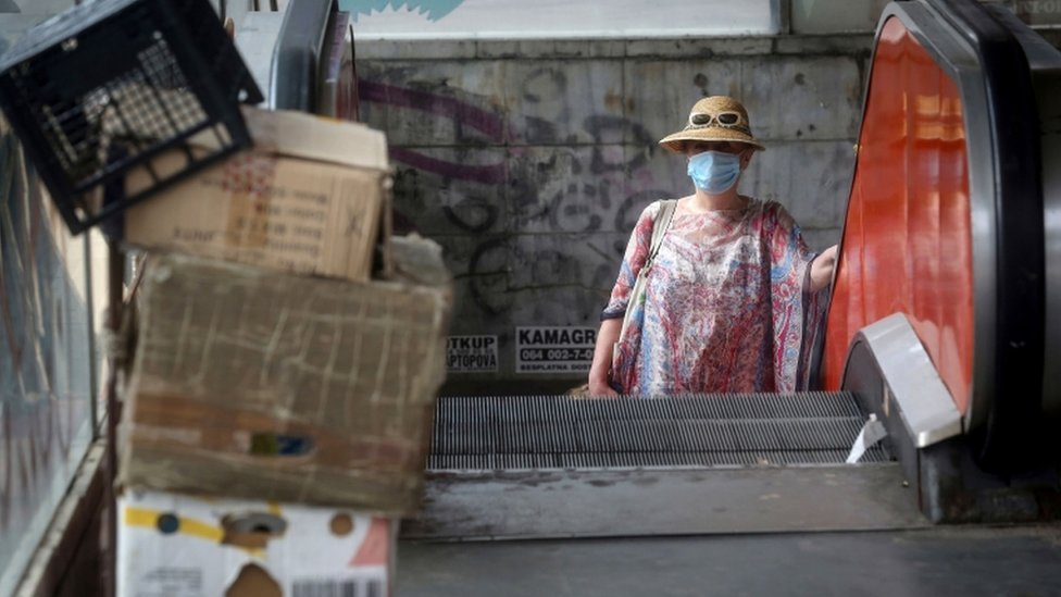 A woman in a face mask on an escalator in Belgrade