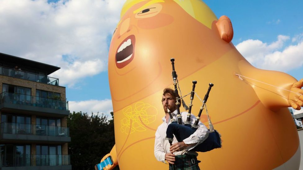 The inflatable Trump Baby with a pipe player in the foreground.