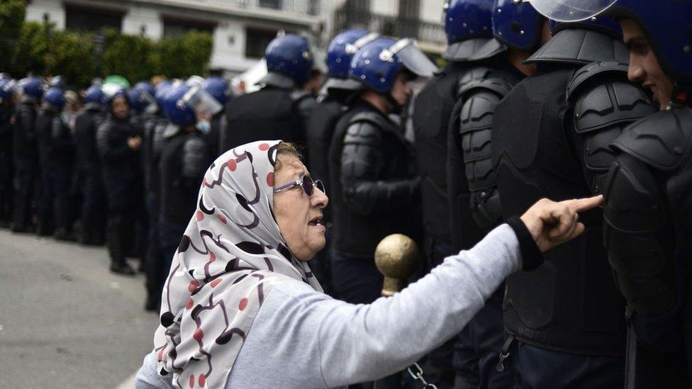 Starija žena priča sa alžirskim snagama bezbednosti tokom skorašnjih protesta