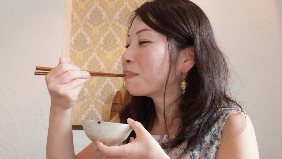 Japanese young woman eating rice