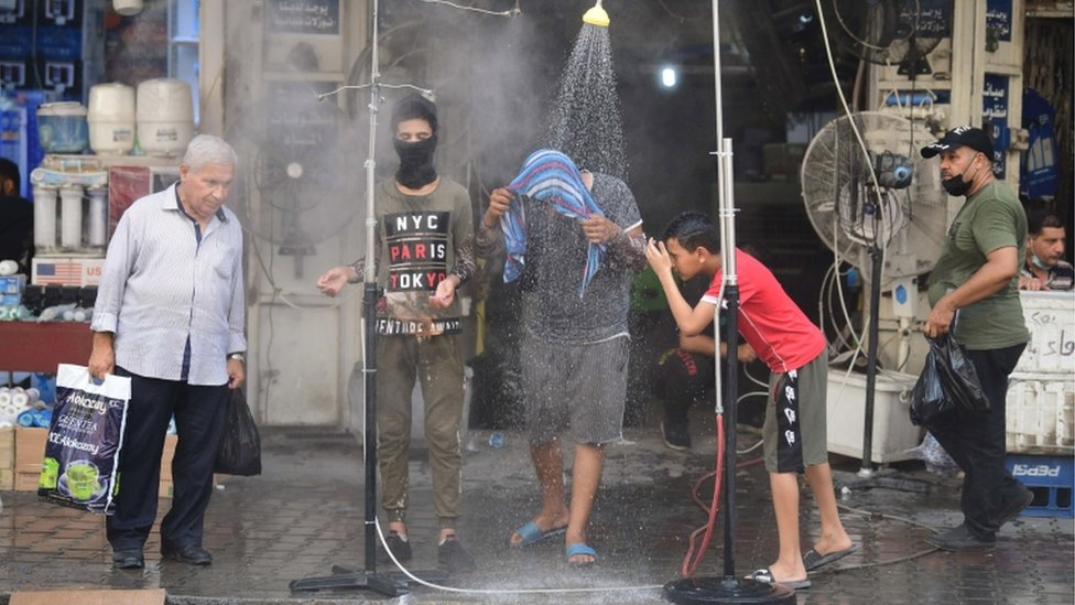 Iraqi men cool off under a public shower at a street in central Baghdad