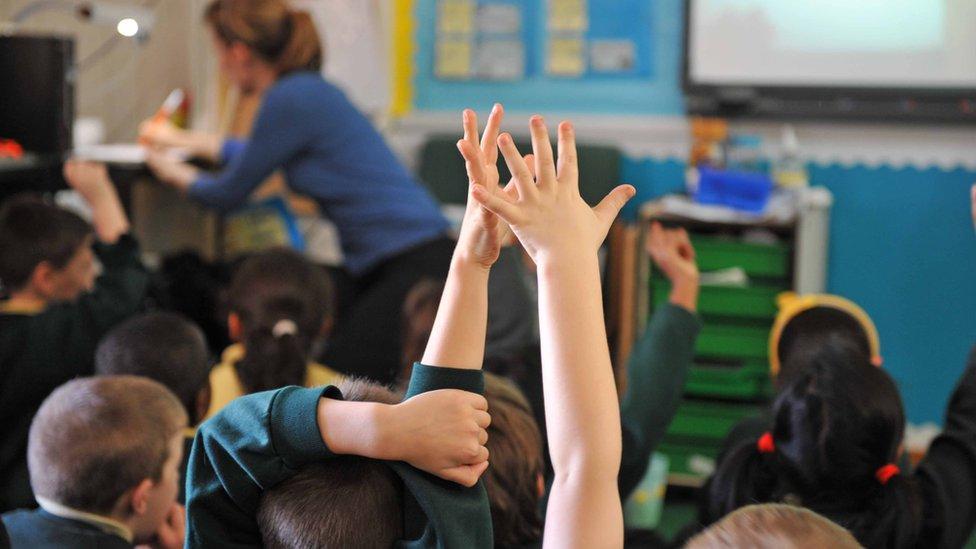 Učionica, podignute ruke đaka