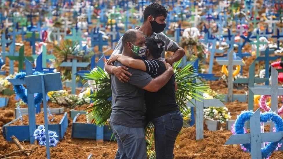 Three people hug at a cemetery
