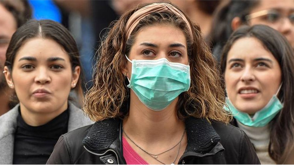 A young woman wearing a face mask is flanked by two others not doing so