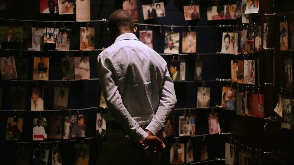 Man looking at pictures of some of the victims of the 1994 Rwandan genocide