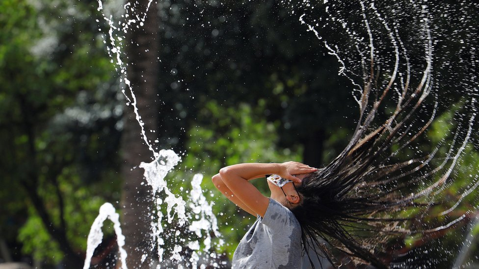 A woman refreshes herself in water at a square in Córdoba, Spain