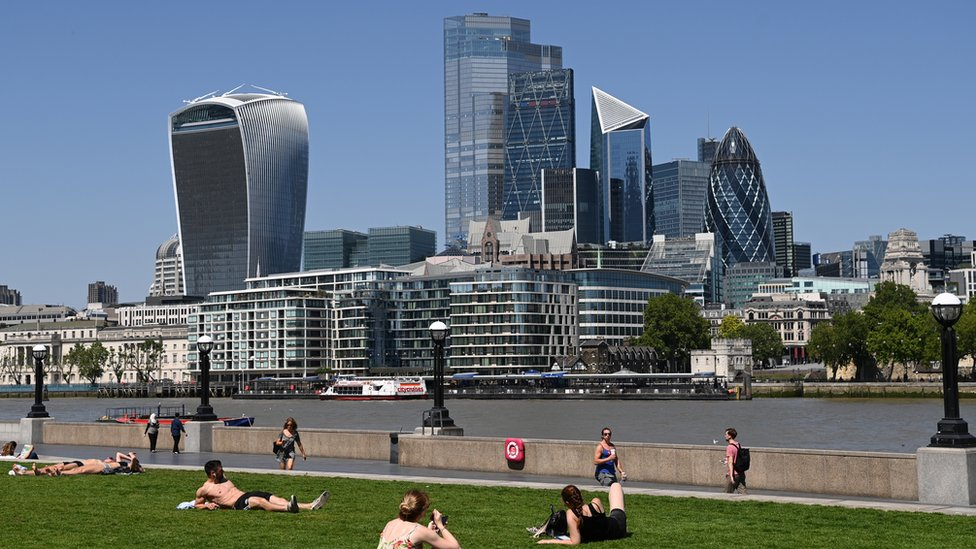 People enjoy the hot weather in by the river Thames in London, Britain