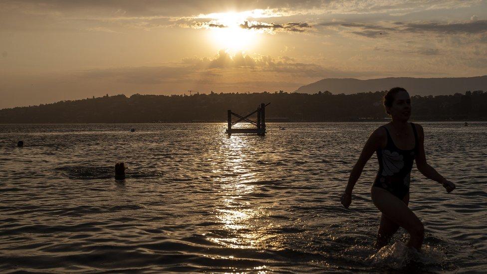 People enjoy bathing at sunrise in the Geneva lake in Geneva, Switzerland