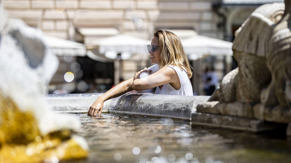 People cool off at a fountain during the heat wave in Rome, Italy