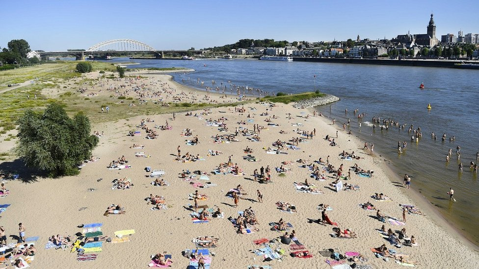 People enjoy the warm weather in the Waal river in Nijmegen, The Netherlands