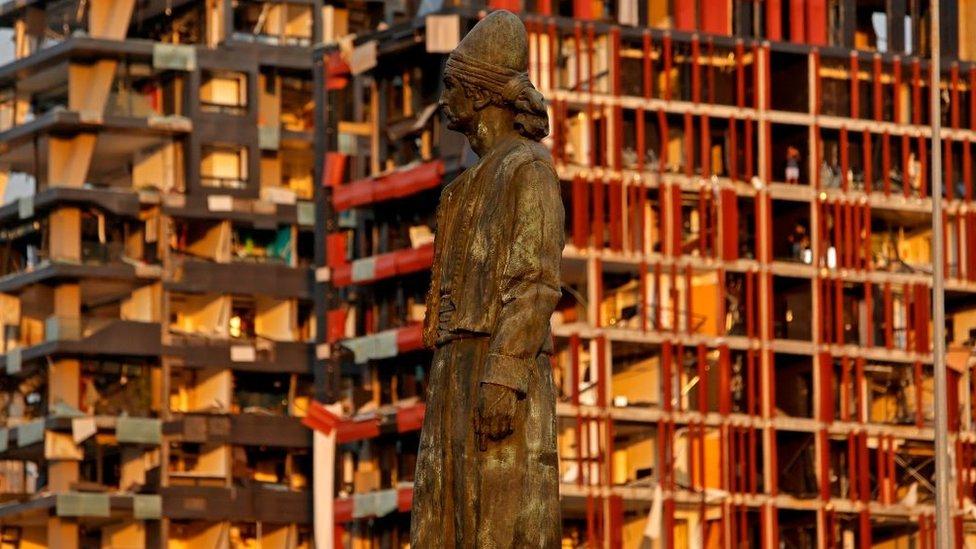 Spomenik Libanskom iseljeniku stoji ispred oštećenih zgrada
