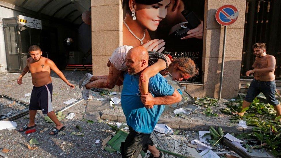 Čovek nosi povređenu devojku u Bejrutu